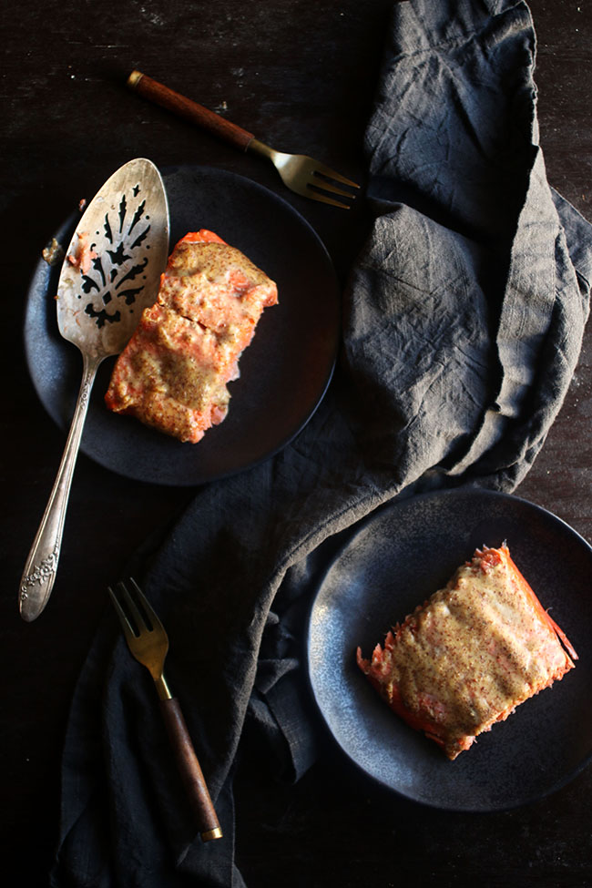 Overhead photo of two dark plates filled with baked salmon on a dark background with a linen napkin on the side