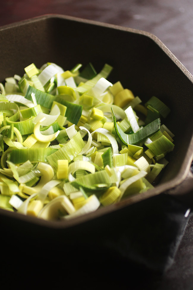 chopped leeks in a cast iron skillet on a brown wooden countertop