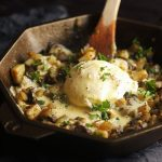 breakfast hash in a cast iron skillet topped with a poached egg