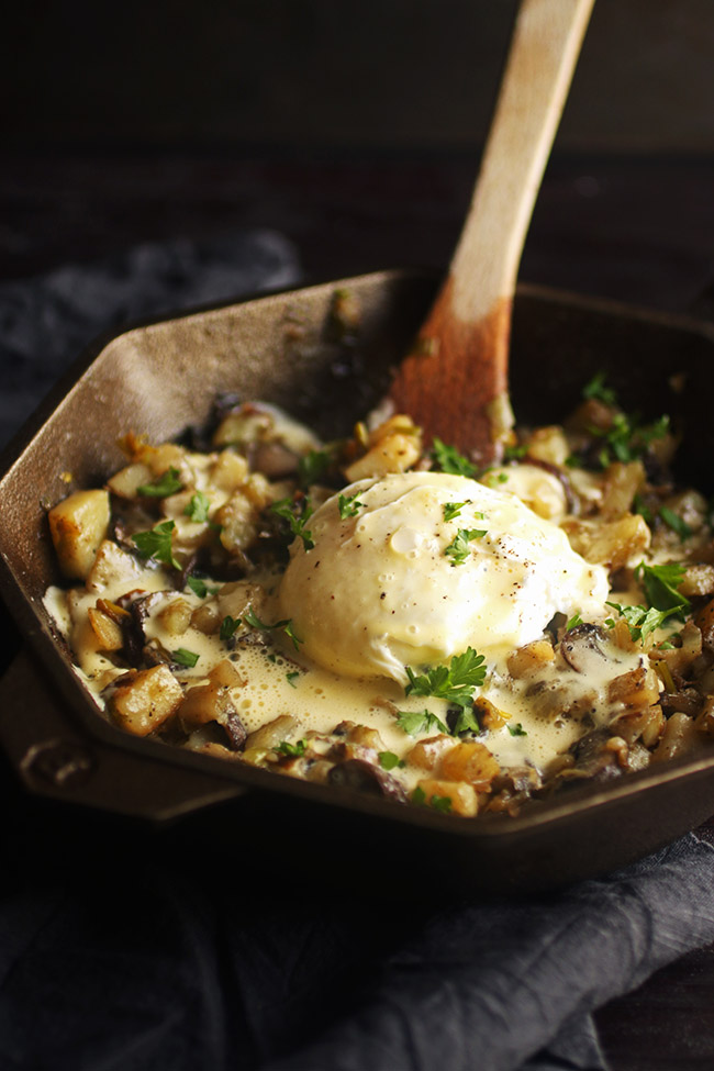 breakfast hash topped with a poached egg and hollandaise sauce in a cast iron skillet with a wooden spoon sticking out of it