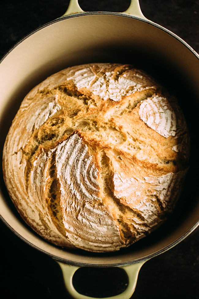 Overhead photo of crusty french bread inside a Dutch oven on a dark background