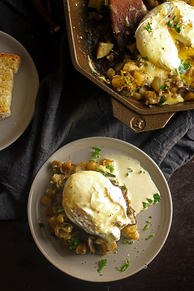 overhead photo of a plate of eggs benedict next to a cast iron skillet filled with leek and mushroom breakfast hash topped with chopped parsley