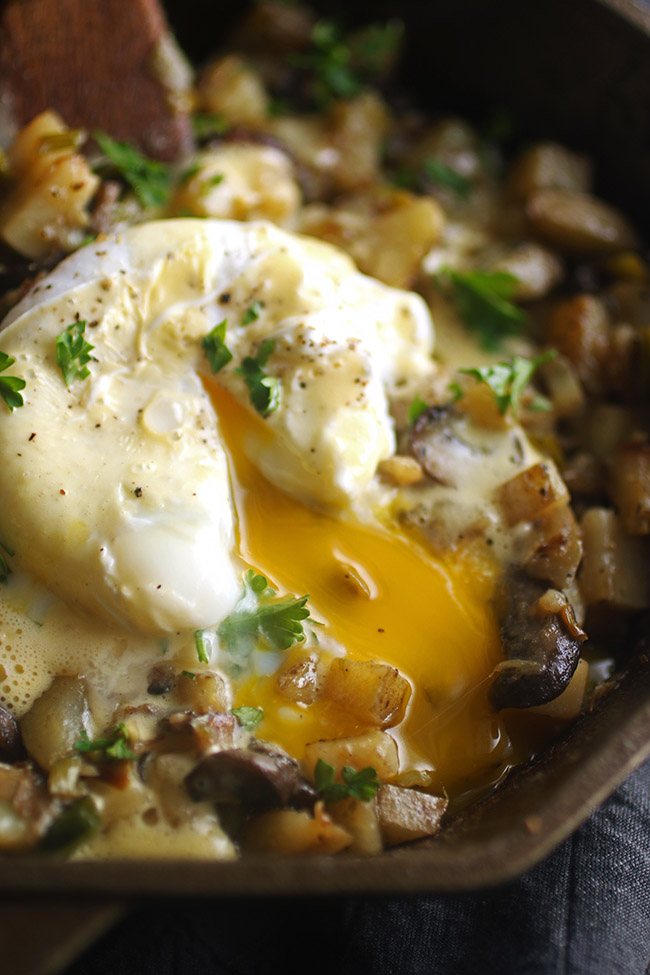 Yolk running out of a poached egg on top of breakfast hash in a cast iron skillet