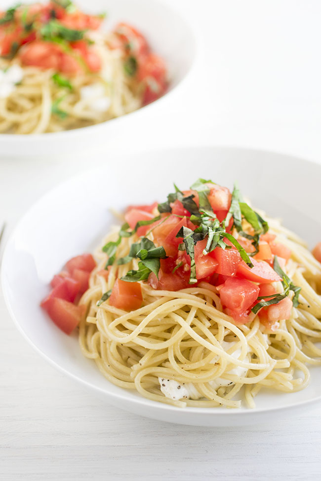 Two white bowls filled with spaghetti noodles topped with diced tomatoes and fresh basil on a white background