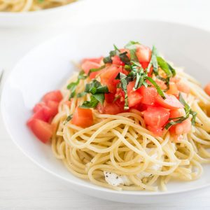 white bowl filled with spaghetti noodles and topped with chicken, diced tomatoes, and chopped basil on a white background