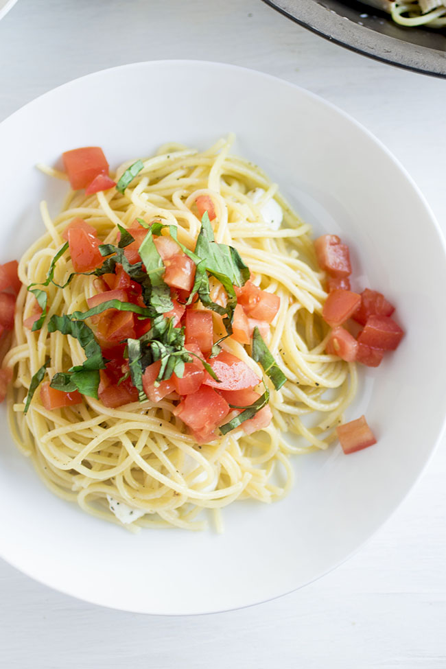 Overhead photo of spaghetti noodles, diced tomatoes, and fresh basil leaves in a white bowl on a white background