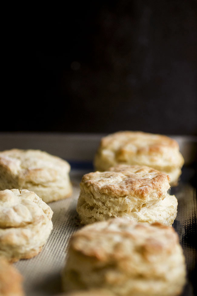 homemade gruyere biscuits on a baking sheet in front of a dark background