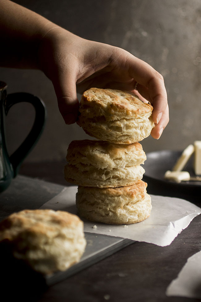 woman's hand adding a biscuit to a stack of biscuits on a dark background