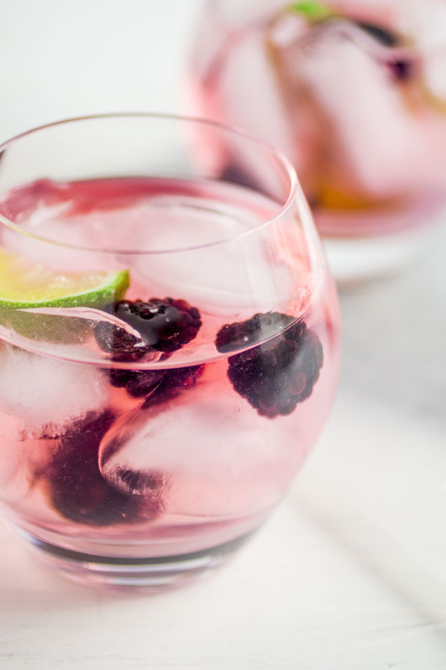 Two cocktail glasses filled with vodka tonics, fresh blackberries, and lime wedges on a white background