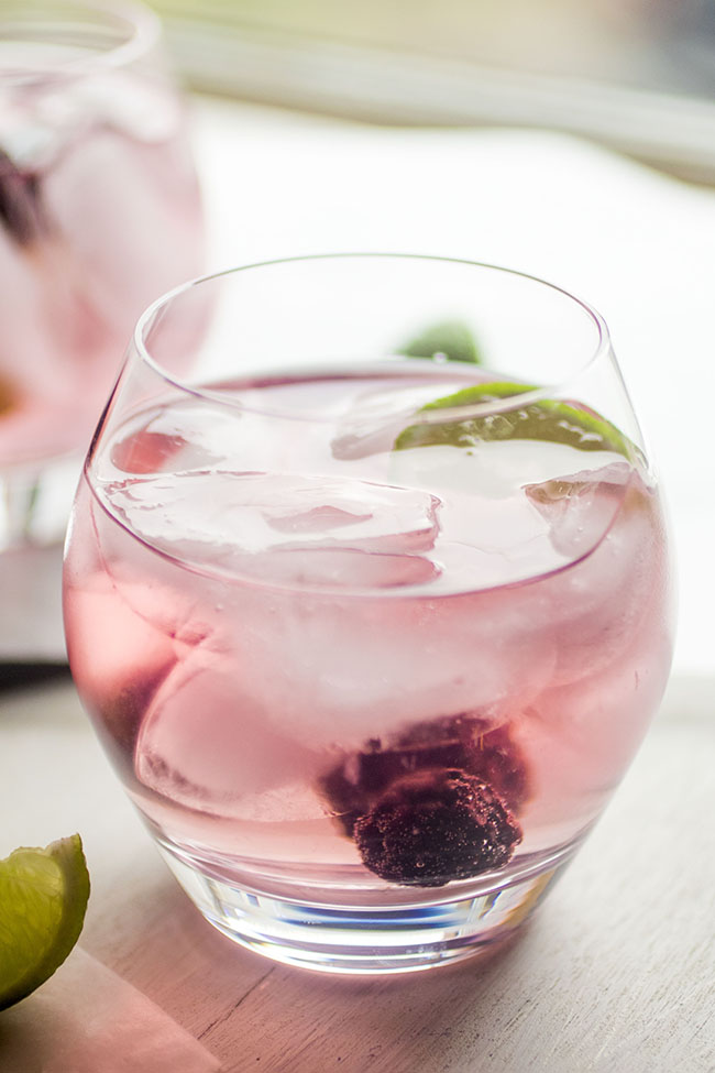 Glass cocktail cup filled with light pink cocktail, fresh blackberries, and a lime wedge