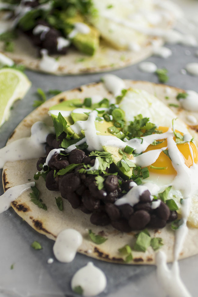 Vegetarian Breakfast Tacos | These vegetarian tacos feature delicious spicy black beans and fried eggs for a hearty Meatless Monday meal! This easy vegetarian breakfast recipe is filling, flavorful, and ready in just 30 minutes.
