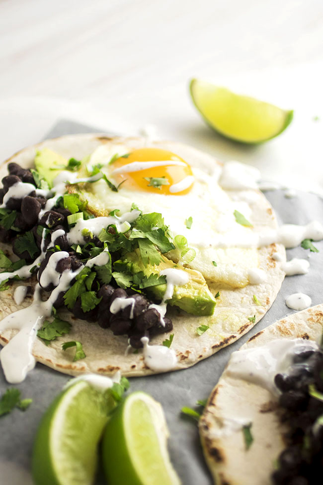 tortilla filled with fried egg, avocados, black beans, and topped with lime crema, cilantro, and green onion