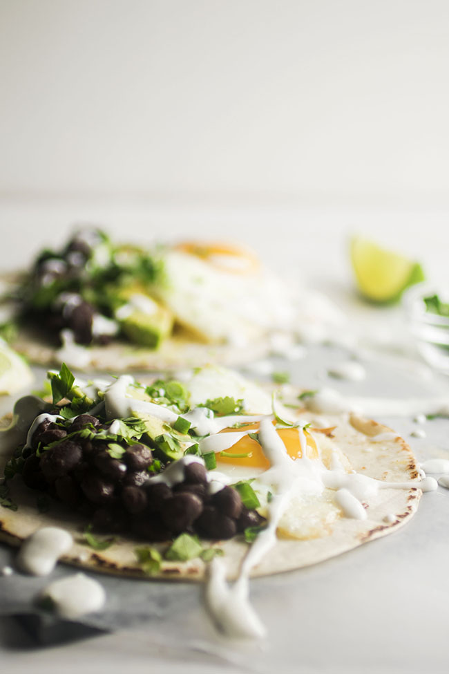 flat tortilla topped with fried egg, avocados, black beans, and topped with lime crema, cilantro, and green onion with a second taco in the background