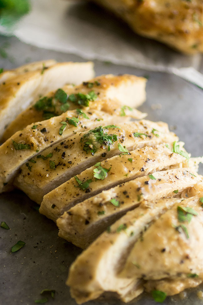 Sliced chicken breast on a slate cutting board topped with chopped parsley