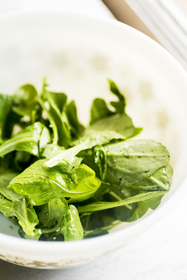 Fresh arugula in a white bowl with olive oil, salt, and pepper