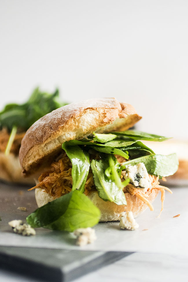 Buffalo chicken sandwich with arugula and blue cheese on a white background