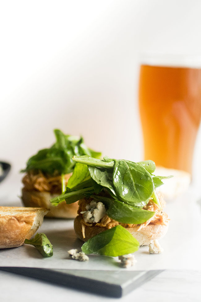 Toasted slider bun topped with slow cooker buffalo chicken and arugula on a white surface with a cup of beer in the background
