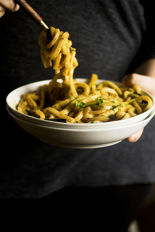 Woman's hands holding a white bowl filled with udon noodles and curry sauce and twirling the pasta with a fork