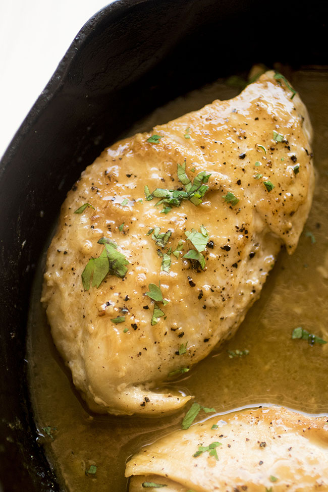 Overhead photo of baked chicken breast in a cast iron skillet with mustard sauce and chopped parsley