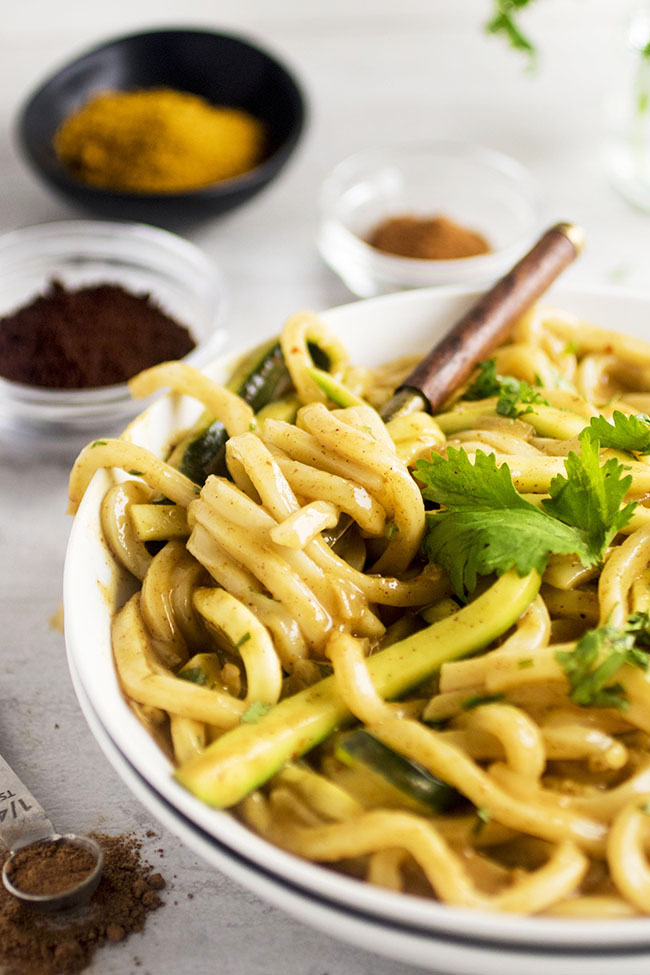 Udon noodles in a white bowl being twirled by a small fork with small bowls of spices in the background
