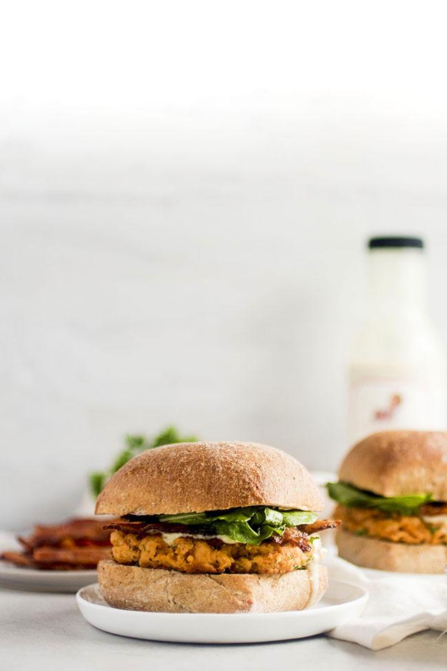 Salmon burgers with wheat ciabatta buns, fresh arugula, and bacon on white plates on a white background