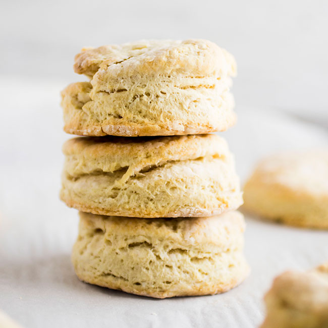 Stack of three biscuits on a baking sheet lined with parchment paper.