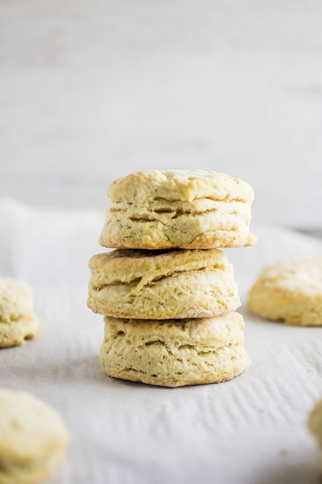 Stack of three vegan biscuits in front of a white background