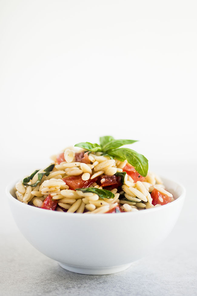 white bowl filled with orzo pasta, chopped tomatoes, and fresh basil