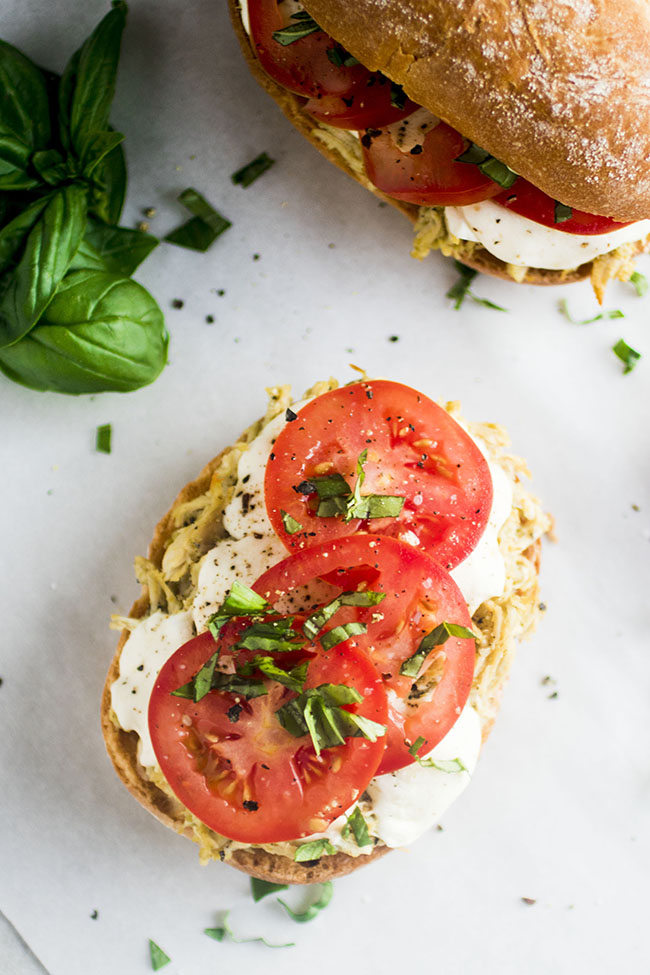 Overhead photo of a sandwich roll topped with shredded chicken and sliced tomatoes on a white background with fresh basil on the side