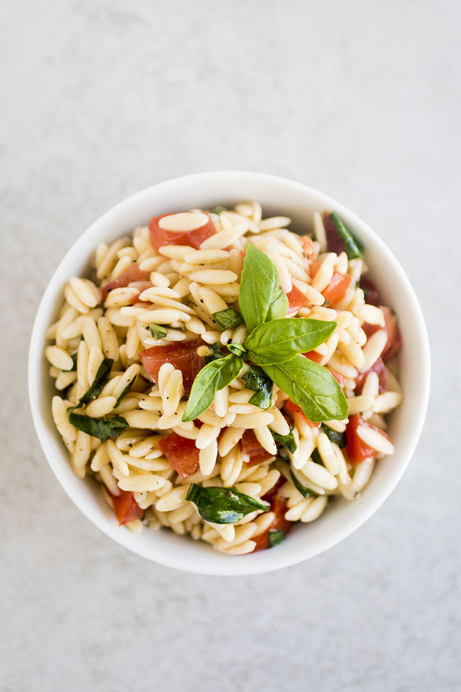 overhead photo of orzo pasta with tomatoes and basil in a small white bowl