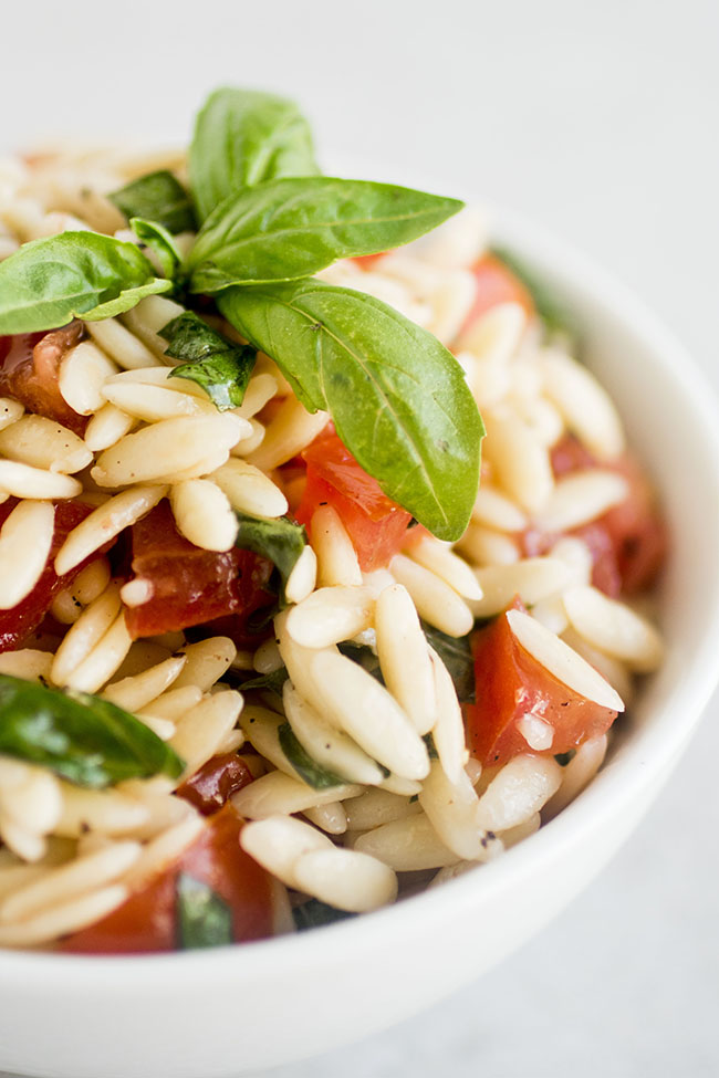 orzo pasta with chopped tomatoes and fresh basil in a white bowl on a white background