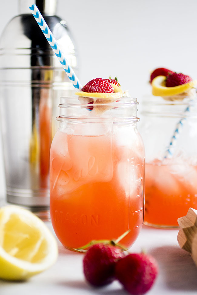 Mason Jars Filled With Strawberry Whiskey Lemonade And A Straw Tail Shaker In Background