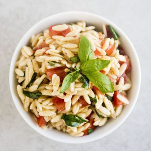 overhead photo of orzo with tomatoes and basil in a white bowl