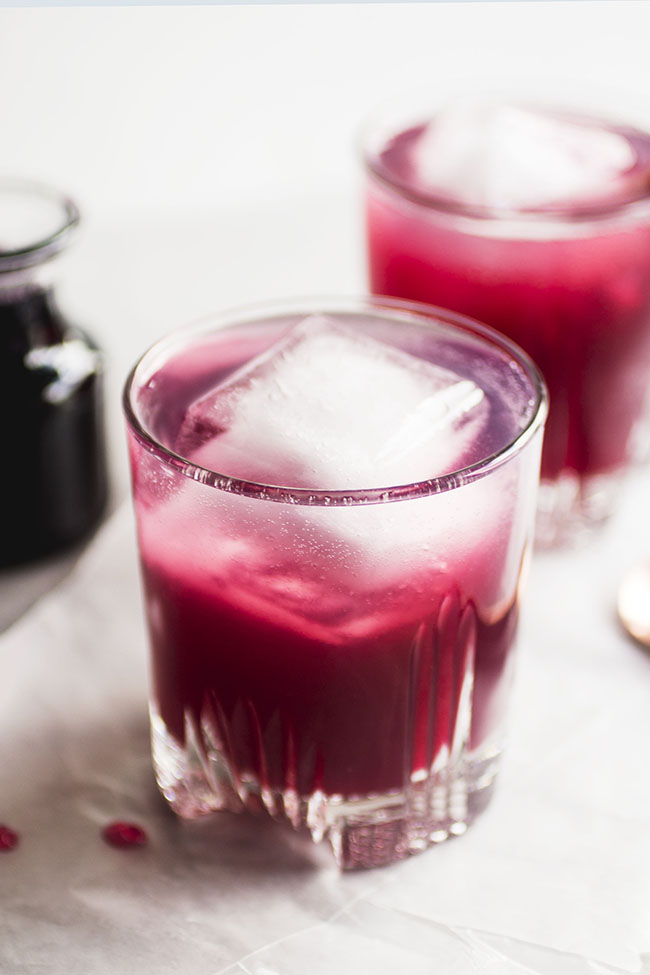 cocktail glasses filled with dark pink cocktail and a large square ice cube on a white background