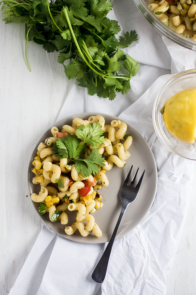 Overhead photo of pasta salad on a grey plate with a small fork next to a bunch of cilantro on a white background