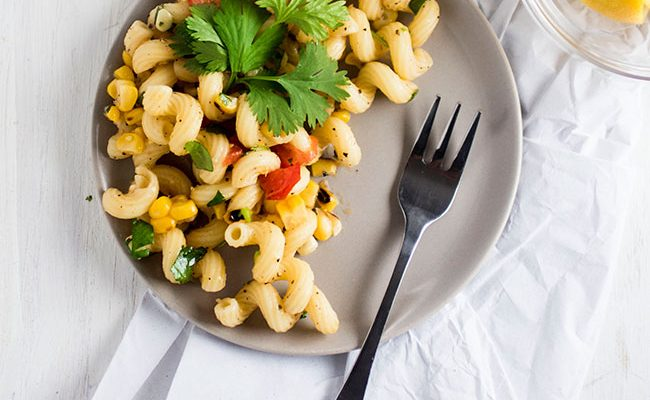 Corn and Tomato Pasta Salad - This easy, vegetarian pasta salad comes together in no time at all and is perfect for summer entertaining! Fresh tomatoes, sweet corn, and cilantro mixed with cavatappi pasta and a fresh lemon pasta sauce make this pasta salad recipe a hit.