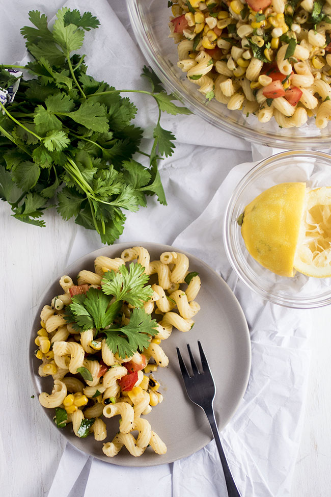 Overhead photo of pasta salad on a grey plate next to fresh cilantro and a lemon
