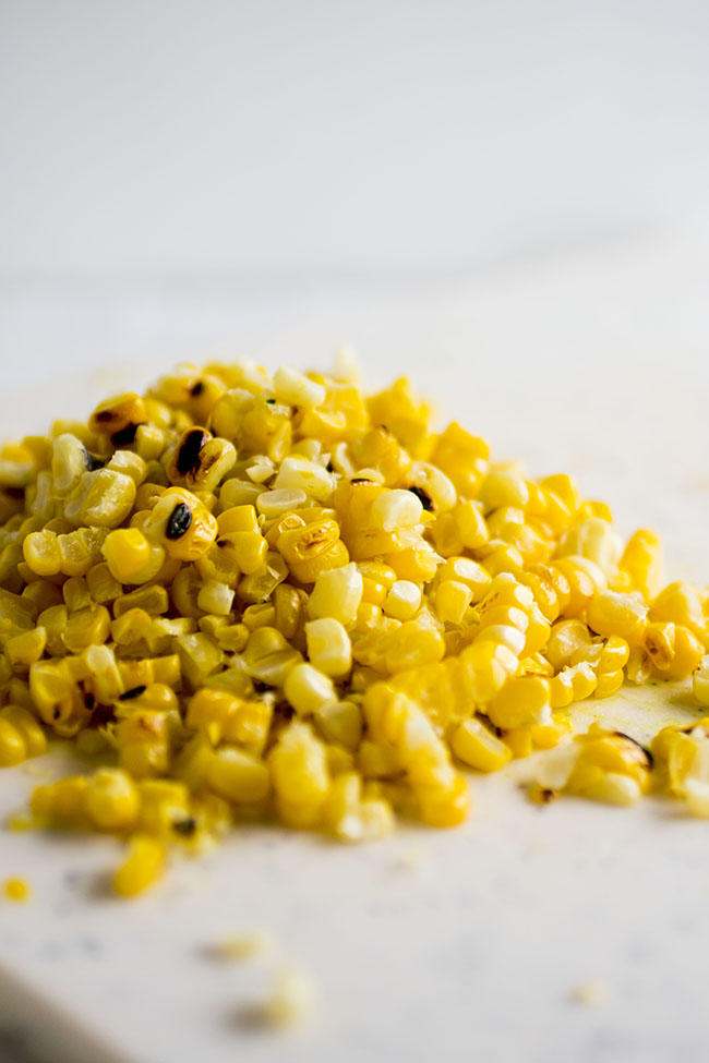 Fresh grilled corn kernels in a pile on a white background