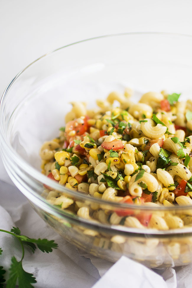 Glass mixing bowl filled with pasta salad with grilled corn and tomatoes on a white background