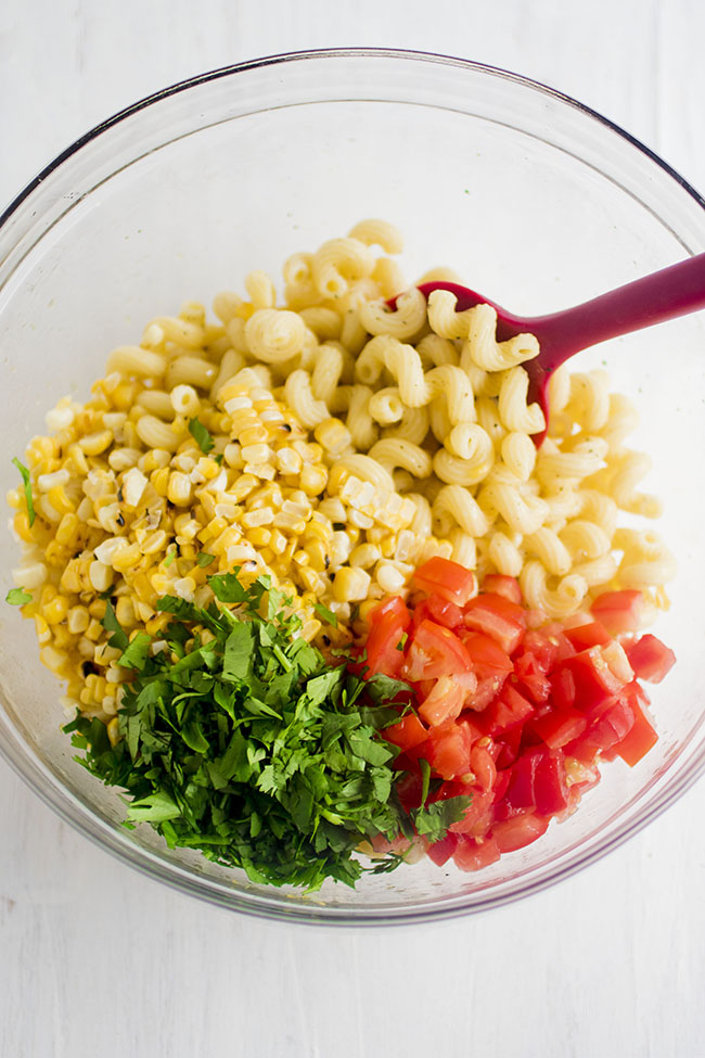 Overhead photo of a glass mixing bowl filled with pasta, grilled corn, cilantro, and chopped tomatoes on a white background