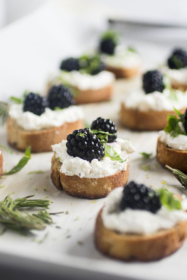 toasted baguette slices topped with goat cheese, blackberries, and basil on a white tray