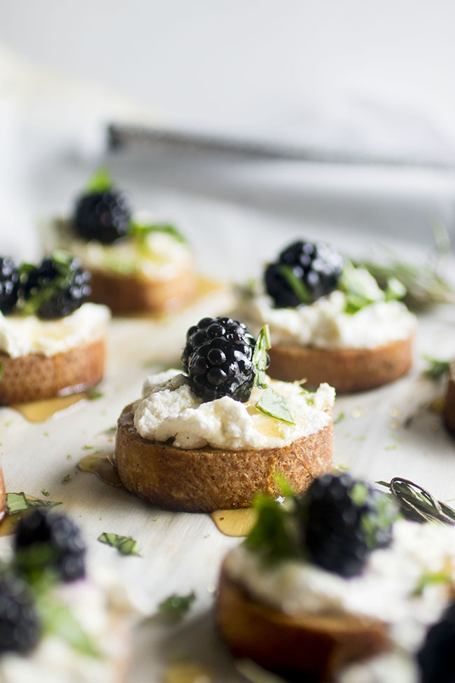 This easy blackberry goat cheese appetizer recipe is perfect for summer entertaining! A simple whipped goat cheese, fresh summer blackberries, basil and a hint of lime make for a decadent bite that's sure to be a hit. Topped with a simple rosemary infused honey for a hint of earthy summer sweetness. Vegetarian.