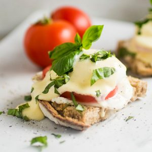 Caprese Eggs Benedict - This easy vegetarian eggs benedict recipe is perfect for your next brunch! Delicious (and foolproof!) homemade hollandaise sauce, fresh mozzarella, summer tomatoes and chopped basil are the perfect accompaniment to crusty sourdough bread and a creamy poached egg. Vegetarian.