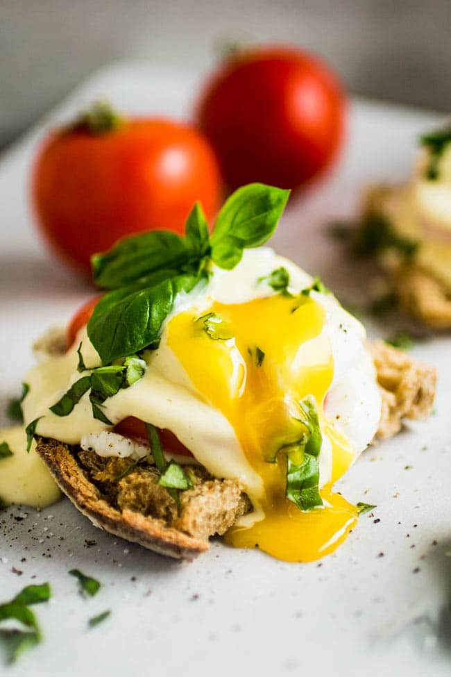 Toast topped with poached egg, hollandaise sauce, and fresh basil, with the egg sliced into and the yolk running out