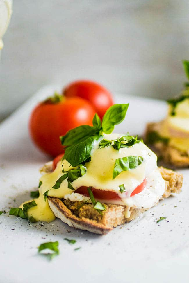 eggs benedict topped with fresh basil on sourdough toast on a white surface with whole tomatoes in the background