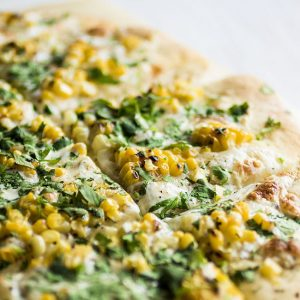 Close up photo of pizza with grilled corn and chopped cilantro on a white background