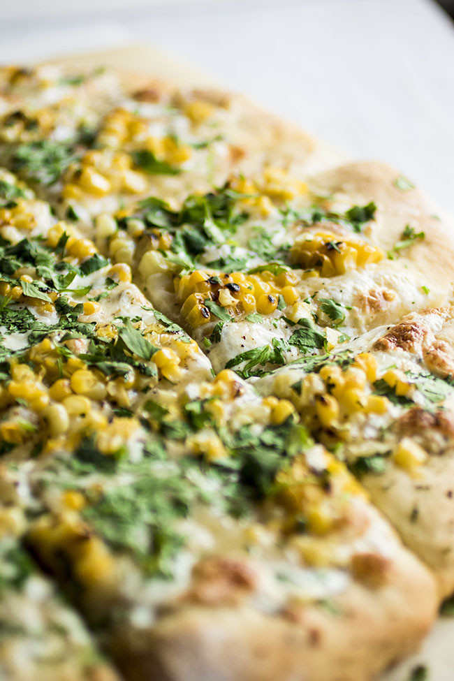 Close up photo of square cut pizza with grilled corn and chopped cilantro on a white background
