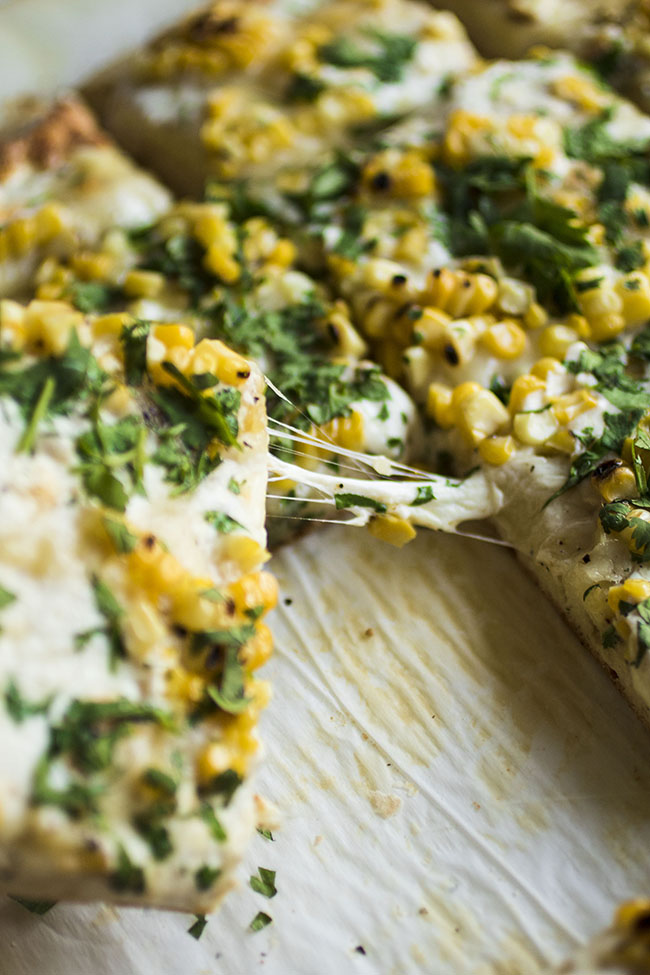 Slice being pulled out of a pizza with a strong of mozzarella cheese topped with grilled corn and chopped cilantro