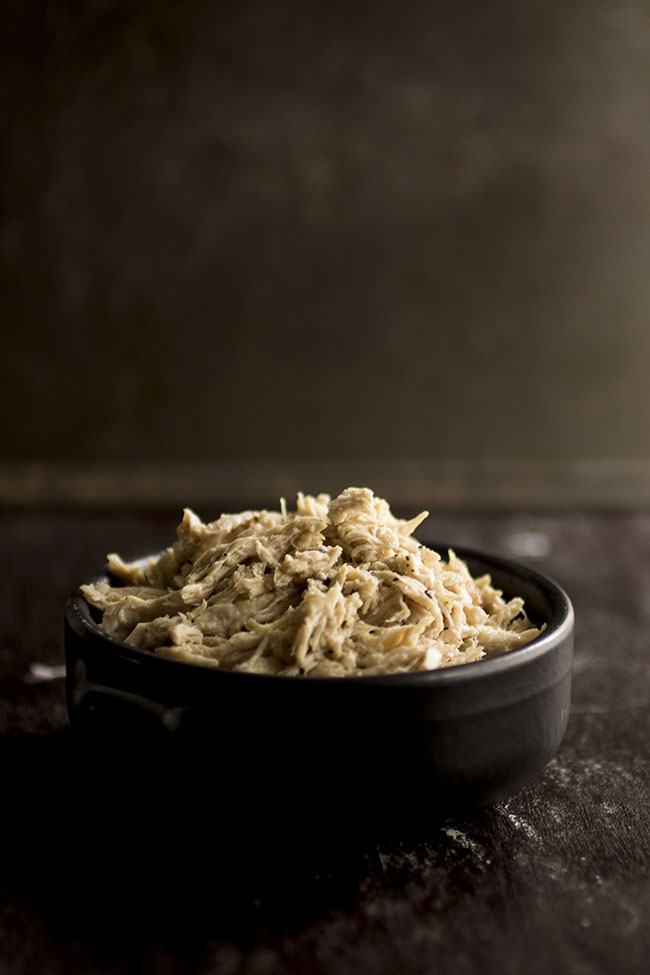 shredded chicken in a shallow black bowl on a dark brown background