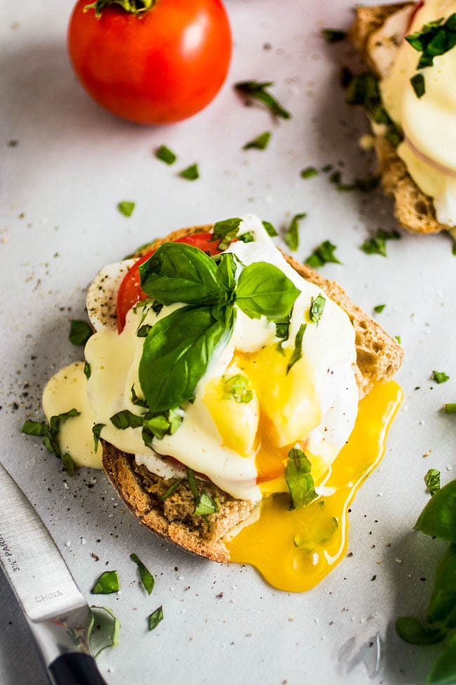 Overhead photo of eggs benedict topped with fresh basil with the egg sliced open and the yolk running out